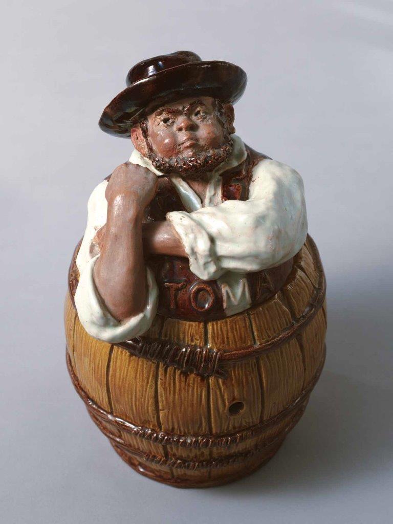 """Caixa de cerâmica """"Toma"""" com o Zé Povinho a fazer um manguito. Rafael Bordalo Pinheiro, 1904. MRBP.CER.0375 © Museu Bordalo Pinheiro, Lisboa."""